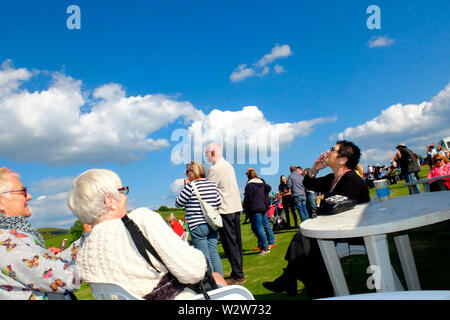 A woman smoking a cigarette at Wolverton Folk and Blues Fair 2019 on the grounds of Wolverton Manor, Shorwell, Isle of Wight, England, UK. - Stock Photo