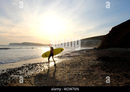 A young man carrying his surfboard under his arm heads out into the sea on foot with the setting sun and Tennyson Down chalk cliffs in the background - Stock Photo