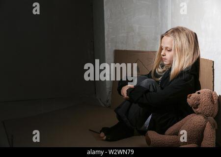 Homeless little girl sitting on floor near wall - Stock Photo