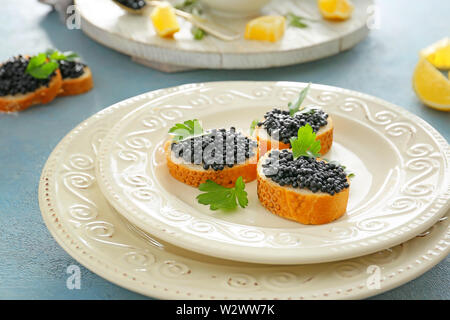 Sandwiches with black caviar on table - Stock Photo