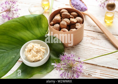 Shea butter with nuts on white wooden background - Stock Photo