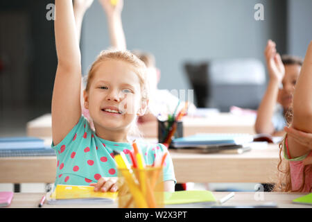 Cute little girl raising hand during lesson in classroom - Stock Photo