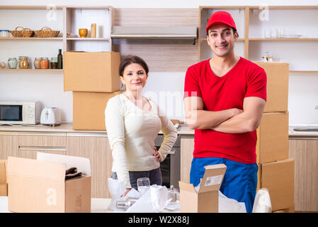 The young male contractor and female customer in moving concept - Stock Photo