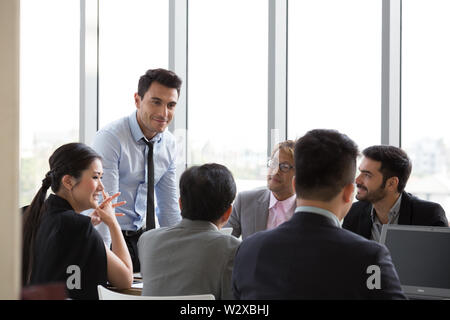 Chief businessman standing at conference table during team meeting, Entrepreneurs making deal starting collaboration at group negotiations teamwork - Stock Photo