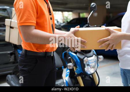 Woman hand accepting a delivery of boxes from deliveryman, Deliver goods by motorcycle service, Fast and Free Transport - Stock Photo