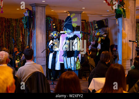 Basel, Switzerland - March 11th, 2019. The carnival Schnitzelbaenggler group called Drey Daags Fliege performing their parody poetry in a restaurant - Stock Photo