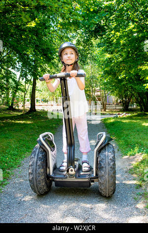 Young girl ride on segway in summer park. - Stock Photo
