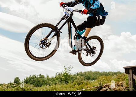 downhill mountain biking rider jumping drop background in sky - Stock Photo