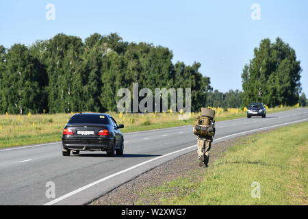 ALTAI TERRITORY, RUSSIA - JULY 11, 2019: Traveller Andrei Sharashkin, 53, follows a road. Military veteran and history teacher from Tyumen, Sharashkin has made up his mind to go on a journey across Russia on foot. He set off in Moscow in 2018 and covered over 7,000km through 20 regions as of today. In his blog Sharashkin shares impressions of his travel, places he went to and people he met in different regions. Kirill Kukhmar/TASS - Stock Photo