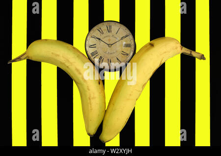 Creative Banana/Clock design on striking yellow and black stripes - Stock Photo