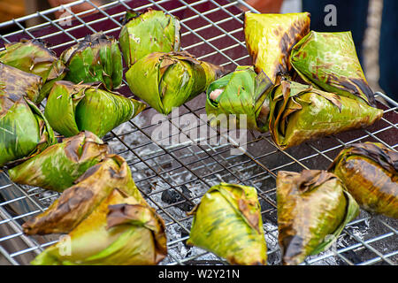 Sticky rice wrapped in banana leaves, roasted on the grill is a popular food in Thailand. - Stock Photo