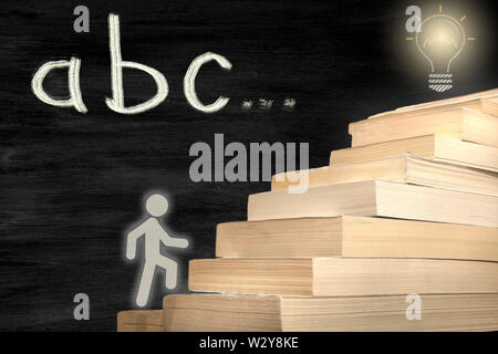 The man figure stepping books. reaching the target by reading. concept photo with abc text - Stock Photo