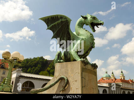 The Dragon statues at the Dragon Bridge and Cathedral of St. Nicholas at the background in center of Ljubljana, Slovenia - Stock Photo