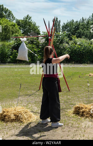 A young girl in a black suit with a red belt shoots from a vintage bow at the target from a bag with a straw. Cosplay festival in nature. Girl warrior - Stock Photo