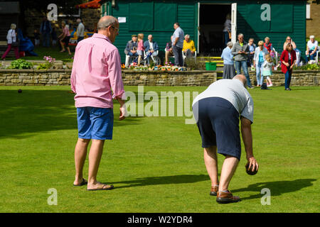 2 men playing target bowls on bowling green at busy fun event (man about to bowl, people watching) - Burley-In-Wharfedale, West Yorkshire, England, UK - Stock Photo