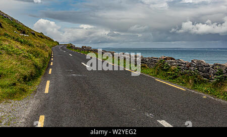 Landscape with the sea and the rural coastal road along the Burren, geosite and geopark, Wild Atlantic Way, cloudy spring day - Stock Photo
