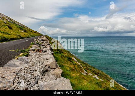 Beautiful landscape with the sea and the rural coastal R477 road along the Burren, geosite and geopark, Wild Atlantic Way, cloudy spring day - Stock Photo