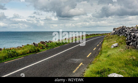 Irish landscape with the sea and the rural coastal R477 road along the Burren, geosite and geopark, Wild Atlantic Way, cloudy spring day - Stock Photo