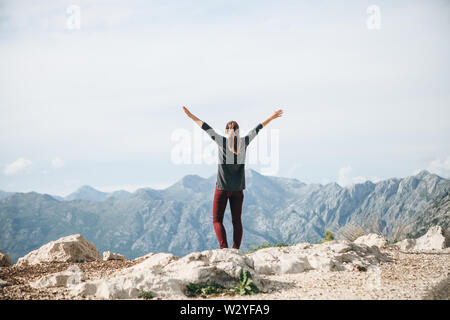 Girl on top of a mountain or hill raises his hands up. She's happy and free.