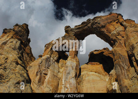 A dark stormy sky adds to the dramatic natural beauty of the Grosvenor double arches in the Staircase-Escalante National Monument, Southern, Utah, USA - Stock Photo