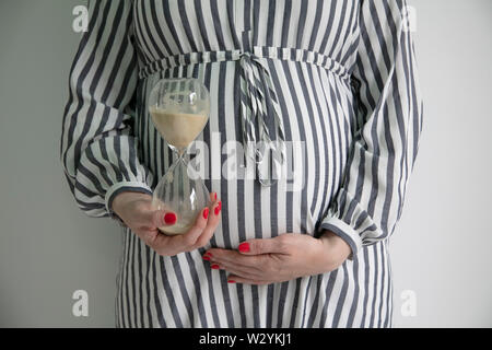 Pregnancy due date concept. Woman holding prgnant belly with an egg timer - Stock Photo