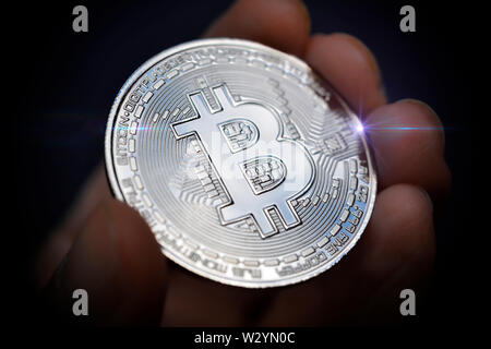 Finger holding Bitcoin coin, virtual currency - Stock Photo