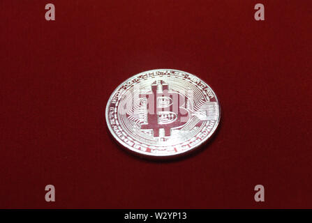 closeup of a silver bitcoin on red velvet background - Stock Photo
