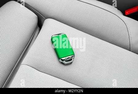 Closeup inside vehicle of wireless green leather key ignition on white leather seat. Wireless start engine key. Car key remote isolated. Modern Car ke - Stock Photo