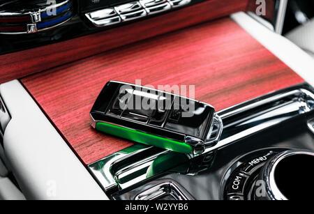 Closeup inside vehicle of wireless green leather key ignition on natural wood panel. Wireless start engine key. Car key remote isolated. Modern Car ke - Stock Photo
