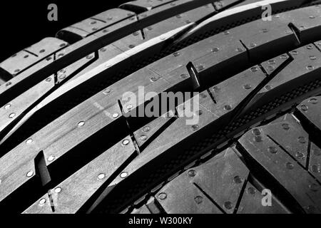 Studio shot of a set of summer car tires on black background. Tire stack background. Car tyre protector close up. Black rubber tire. Brand new car tir - Stock Photo