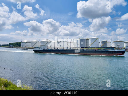 View on oil storage tanks in industrial area along the Caland canal near Rotterdam - Stock Photo