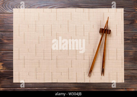two sushi chopsticks with empty brown bamboo mat or wood plate on wooden Background Top view with copy space. empty asian food background. - Stock Photo