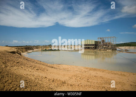 Managing & transporting of titanium mineral sands at mine site.  Mining by dredging in freshwater pond. Dredges pump sand into wet concentrator plant. - Stock Photo
