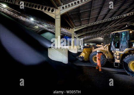 Mining, managing & transporting of titanium mineral sands. Inside ilmenite and rutile storage warehouse. Moving ilmenite from bunker to load conveyor. - Stock Photo