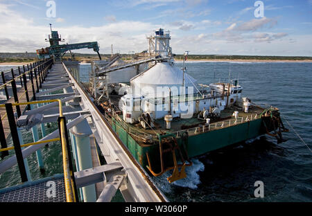 Mining, managing & transporting of titanium mineral sands. Port operations with barge loading & marine jetty work before transhipping product to OGV. - Stock Photo