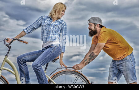Woman rides bicycle sky background. Service and assistance. Man helps keep balance ride bike. Girl cycling while man support her. Support helps believe in yourself. Support and friendship. - Stock Photo