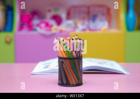 Pen, pencil and accessory in black basket isolated on blured background .Colored pencils in a pencil case on blured background - Stock Photo