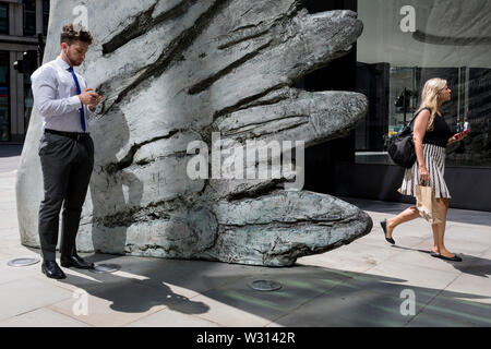 A financial industry businessman checks messages as a lady walks the other side of the sculpture entitled City Wing on Threadneedle Street in the City of London, the capital's financial district (aka the Square Mile), on 11th July 2019, in London, England. City Wing is by the artist Christopher Le Brun. The ten-metre-tall bronze sculpture is by President of the Royal Academy of Arts, Christopher Le Brun, commissioned by Hammerson in 2009. It is called 'The City Wing' and has been cast by Morris Singer Art Founders, reputedly the oldest fine art foundry in the world. - Stock Photo
