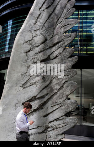 A financial industry buusinessman checks messages beneath the sculpture entitled City Wing on Threadneedle Street in the City of London, the capital's financial district (aka the Square Mile), on 11th July 2019, in London, England. City Wing is by the artist Christopher Le Brun. The ten-metre-tall bronze sculpture is by President of the Royal Academy of Arts, Christopher Le Brun, commissioned by Hammerson in 2009. It is called 'The City Wing' and has been cast by Morris Singer Art Founders, reputedly the oldest fine art foundry in the world. - Stock Photo