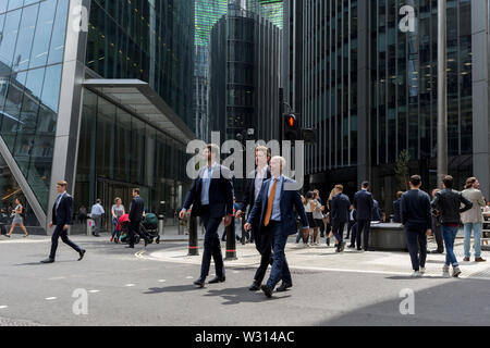 City workers cross Leadenhall in the City of London, the capital's financial district (aka the Square Mile), on 10th July 2019, in London England. - Stock Photo