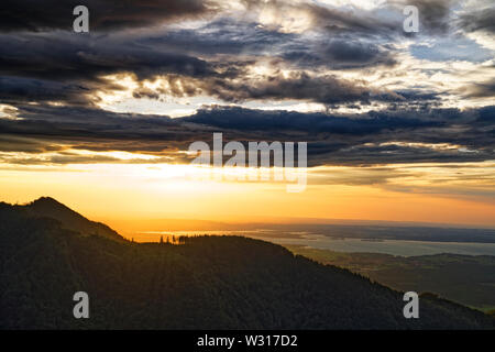 Beautiful sunset over lake Chiemsee with cloudy sky on Hochfelln mountain - Stock Photo
