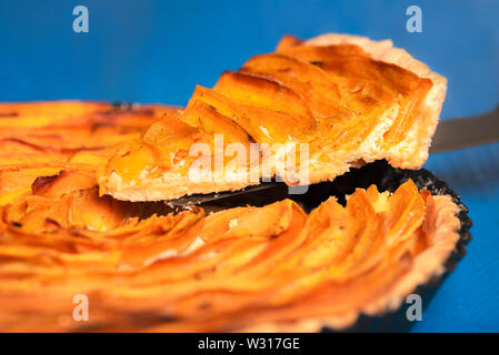 Macro image of a sweet potato tart with a portion sliced, on blue background. American autumn pie, sliced in-tray. Homemade traditional food. - Stock Photo