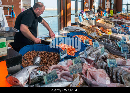 Counter with fresh fish and shrimps on display at covered fish market in the port at seaside resort Port-en-Bessin, Calvados, Normandy, France - Stock Photo