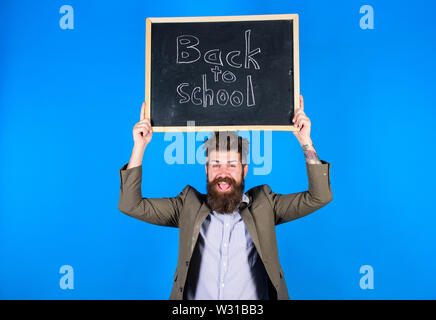 Teacher bearded man holds blackboard with inscription back to school blue background. Teaching stressful occupation. Do not be upset. Teacher with tousled hair stressful about school year beginning. - Stock Photo