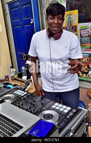 Black female DJ setting up music outside shop window on two mixing decks at Bristol St Paul's carnival festival - Stock Photo