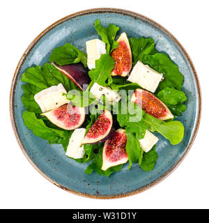 Plate with figs, cheese and greens on white background - Stock Photo