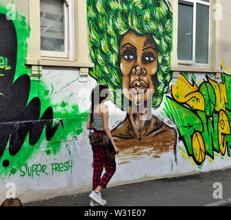 Woman walking away past wall with graffiti wall art in St Paul's Bristol during local carnival - Stock Photo