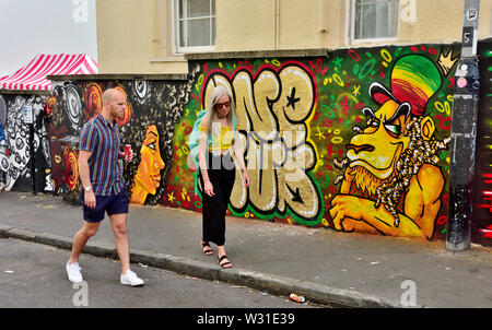 Two people walking along road in St Paul's Bristol with street art behind during carnival time - Stock Photo