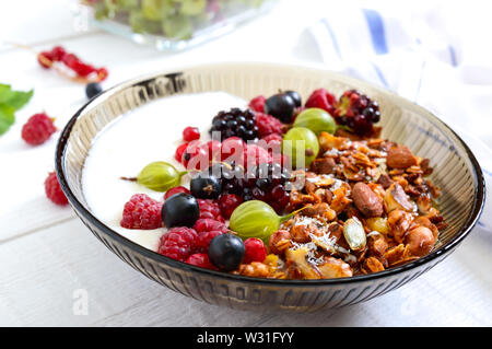 Yogurt, granola, fresh berries in a bowl on a white wooden background. Delicious and healthy breakfast. Proper nutrition. Dietary menu. - Stock Photo