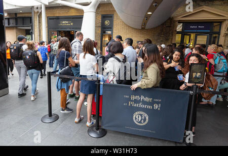 Harry Potter fans queuing in a queue outside the Kings Cross Station Harry Potter shop at Platform 9 3/4, Kings Cross Rail station, London UK - Stock Photo